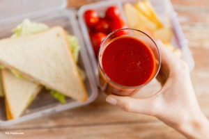 healthy eating, dieting and people concept - close up of woman hand holding fresh tomato juice glass over food in plastic container at home